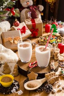 Boisson de lait de poule de noël et du nouvel an dans des tasses en verre sur un support en bois sur la table avec des cadeaux, des biscuits de noël, des bougies, des bonbons et des branches d'arbres de noël.