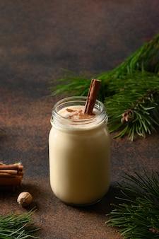 Boisson de lait de poule de noël en pot mason sur fond marron