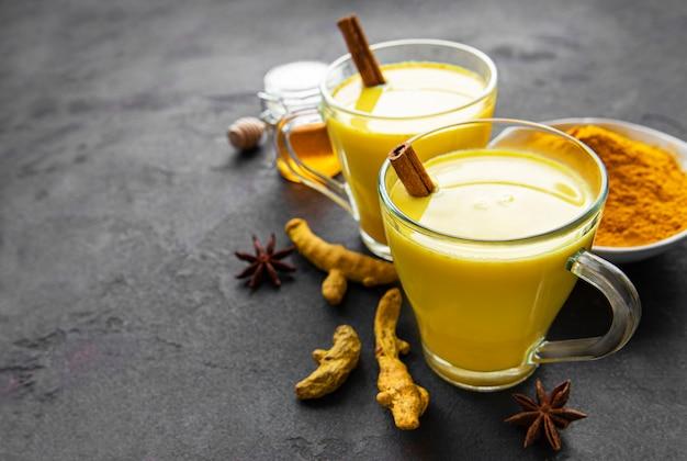 Boisson de latte au curcuma jaune. lait doré à la cannelle, curcuma, gingembre et miel sur fond de pierre noire.
