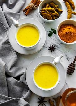 Boisson de latte au curcuma jaune. lait doré avec cannelle, curcuma, gingembre et miel sur une surface en marbre blanc.