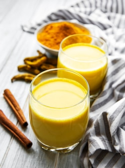 Boisson de latte au curcuma jaune. lait doré avec cannelle, curcuma, gingembre et miel sur table en marbre blanc.