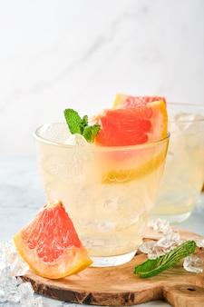 Boisson à la limonade à base de pamplemousse, d'eau gazeuse et de feuilles de menthe avec de la glace sur une surface de béton bleu clair. vue de dessus.