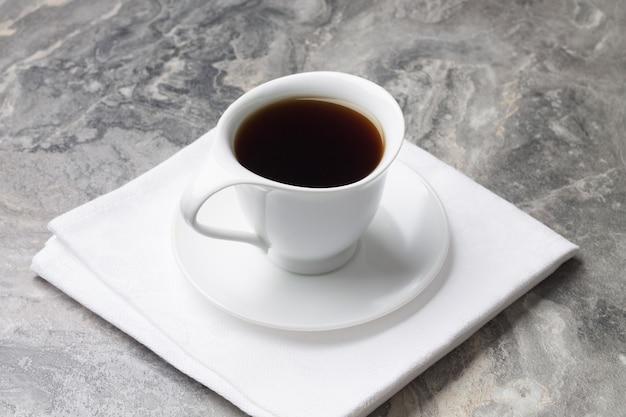 Boisson naturelle de chicorée dans une tasse blanche et soucoupe sur serviette.