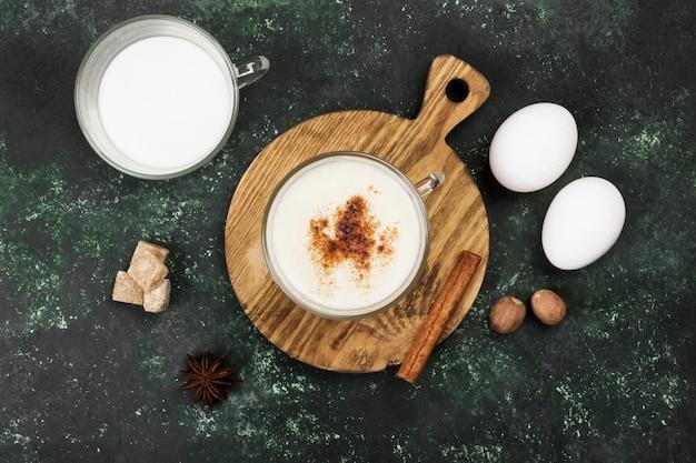 Boisson de noël lait de poule et ingrédients sur une surface verte