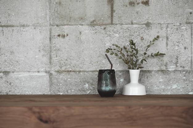 Boisson noire à base de charbon et de lait sur une table en bois de style vintage avec un pot de décoration de feuilles de plantes sèches.