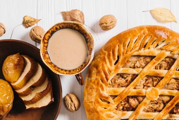 Boisson et noix près de pommes au four et de tarte