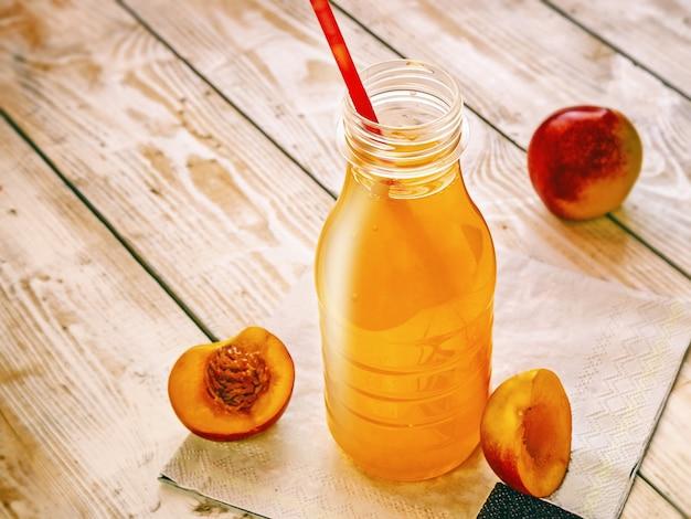 Boisson non alcoolisée aux fruits dans une bouteille avec des morceaux de fruits nectarine sur bois