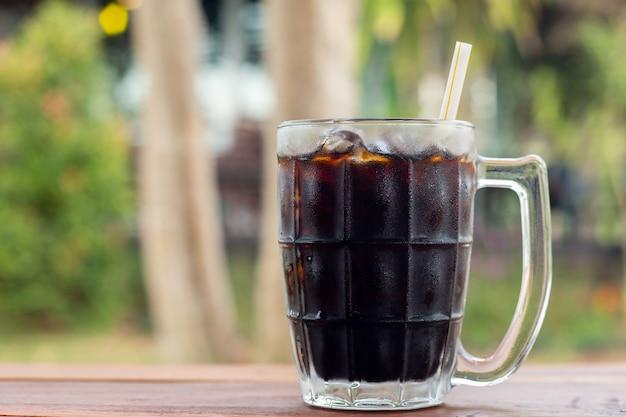 Boisson non alcoolisée cola glacé dans une vue de côté en verre sur le bureau en bois avec fond porte sur vert naturel pendant la journée en été