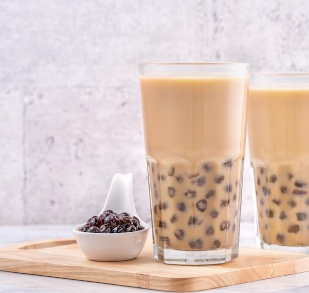 Boisson populaire de taiwan - thé au lait à bulles avec boule de perles de tapioca dans un verre à boire sur fond de plateau en bois table blanche en marbre, gros plan, espace de copie