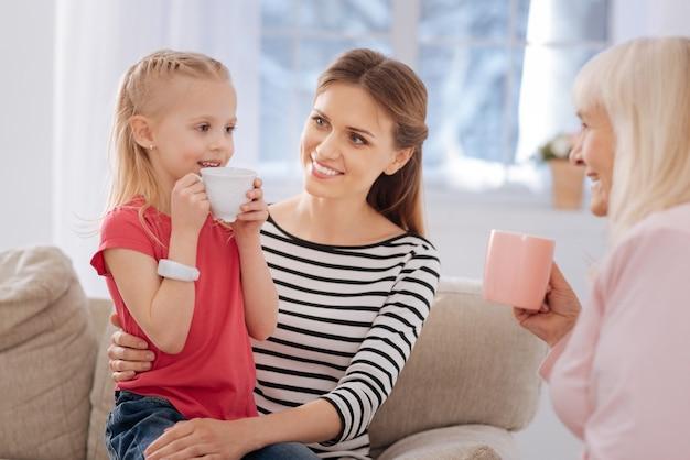 Boisson préférée. belle fille mignonne joyeuse tenant une tasse de thé et souriant tout en regardant sa grand-mère