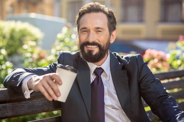 Boisson préférée. gros plan d'un homme d'affaires professionnel joyeux reposant sur le banc tout en exprimant sa joie