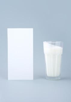 Boisson probiotique, babeurre ou yaourt. kéfir en verre sur fond bleu minimaliste. bactéries santé intestinale, produits fermentés pour le tractus gastro-intestinal. verticale. maquette.