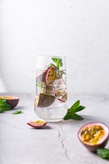 Boisson rafraîchissante avec cocktail de fruits de la passion avec des fruits tropicaux sur une surface claire avec des feuilles de menthe verte en position verticale