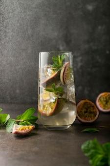 Boisson rafraîchissante avec cocktail de fruits de la passion avec des fruits tropicaux sur une surface sombre avec des feuilles de menthe verte en position verticale