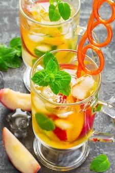 Boisson rafraîchissante en été thé sucré à la pêche avec glace et menthe