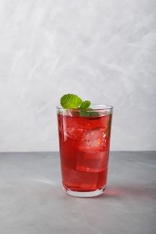 Boisson rafraîchissante non alcoolisée d'été rouge avec de la glace ou du thé glacé aux fruits, gros plan