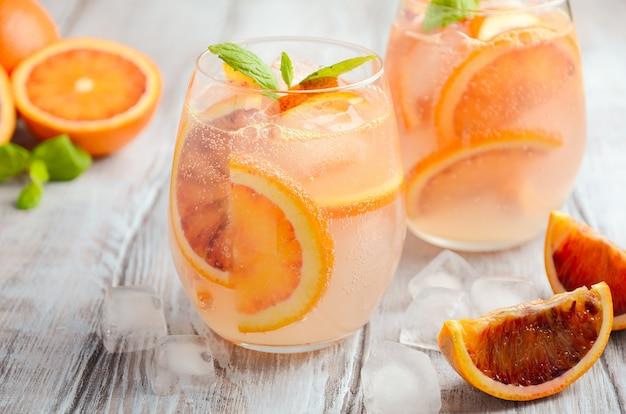 Boisson rafraîchissante avec des tranches d'orange sanguine dans un verre sur un bois.