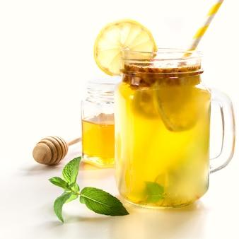 Boisson saine d'argousier, citron et menthe dans un bocal à conserves blanc.