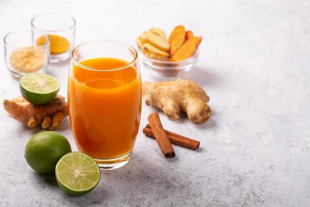Boisson saine de racines de curcuma et de gingembre et de la chaux dans un verre sur fond blanc.