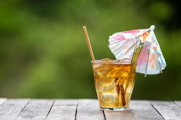Boisson saine et rafraîchissante de cannelle et de tiges de citronnelle sur une table en bois dans un jardin tropical.