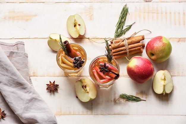 Boisson savoureuse aux épices et tranches de pomme dans des verres sur bois clair