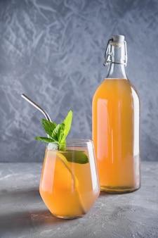 Boisson savoureuse saine kombucha en bouteille et verre à la menthe.