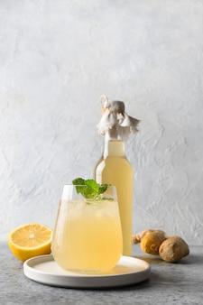 Boisson savoureuse saine kombucha maison en bouteille et verre avec garniture de citron menthe
