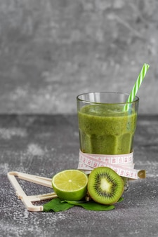 Boisson de smoothie frais dans un grand verre en verre avec un centimètre enroulé autour et un pied à coulisse à côté, entouré de fruits sur un fond de béton gris. le concept d'une bonne nutrition, perte de poids