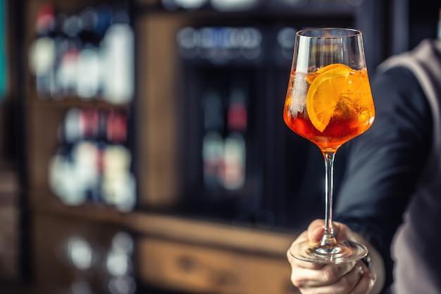 Boisson spritz aperol. main de barman tenant un verre avec une boisson aperol spritz.