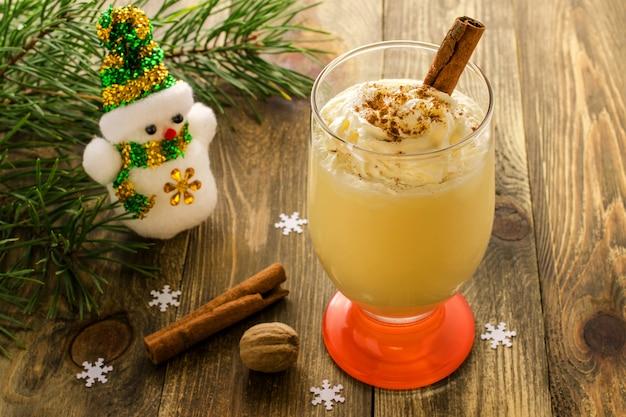 Boisson sucrée maison de noël: lait de poule à la cannelle, muscade et crème fouettée.