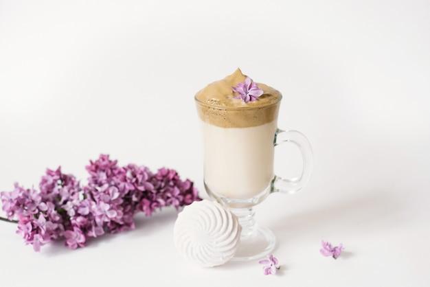 La boisson tendance de dalgon est le café. tasse à café, lilas et guimauve sur fond blanc