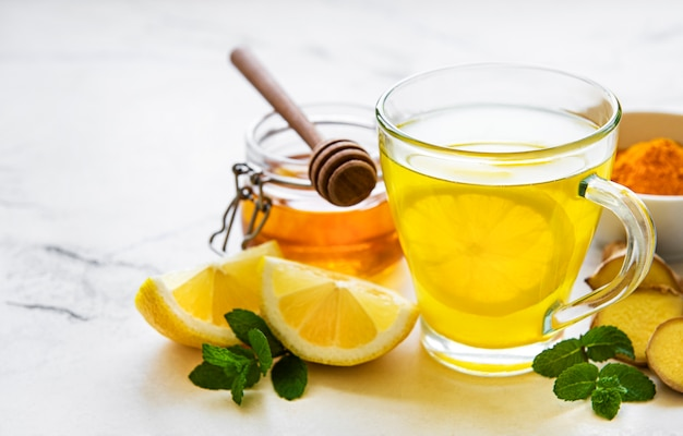 Boisson tonique énergétique au curcuma, gingembre, citron et miel sur un bois blanc