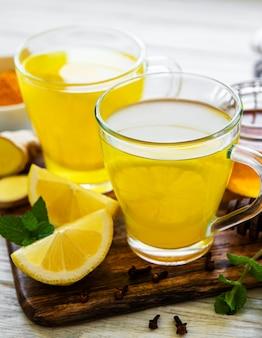 Boisson tonique énergétique au curcuma, gingembre, citron et miel sur un fond en bois blanc