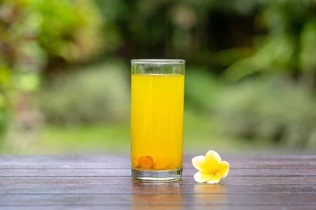 Boisson tonique énergétique avec curcuma, gingembre, citron et miel en verre, fond nature, gros plan