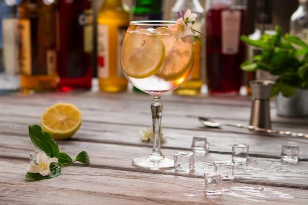 Boisson avec tranche de citron. verre à vin décoré de fleur. agrumes juteux et glace. goût rafraîchissant de tom collins.