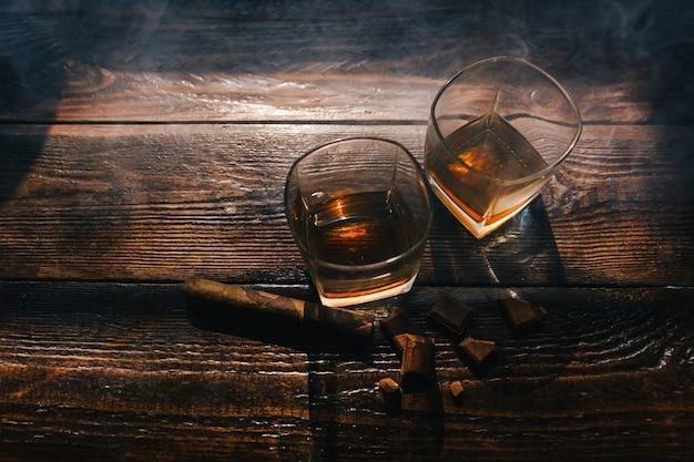 Boissons alcoolisées et cigares sur fond en bois. concept de mode de vie de luxe indulgent pour hommes riches