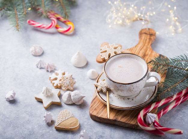 Boissons au cacao au chocolat chaud avec du pain d'épice dans une tasse blanche de noël sur une surface grise. boisson chaude traditionnelle des fêtes, cocktail festif à noël ou nouvel an. vue de dessus