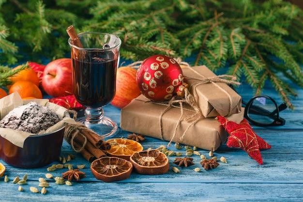 Boissons au vin chaud avec un arrangement épicé et sucré, tourné sur une vieille table en bois