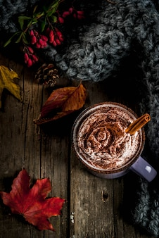 Boissons d'automne, chocolat chaud ou cacao avec de la crème fouettée et des épices (cannelle, anis), sur l'ancienne table en bois rustique, avec une couverture confortable et chaleureuse, des baies de foin et des feuilles vue de dessus du fond