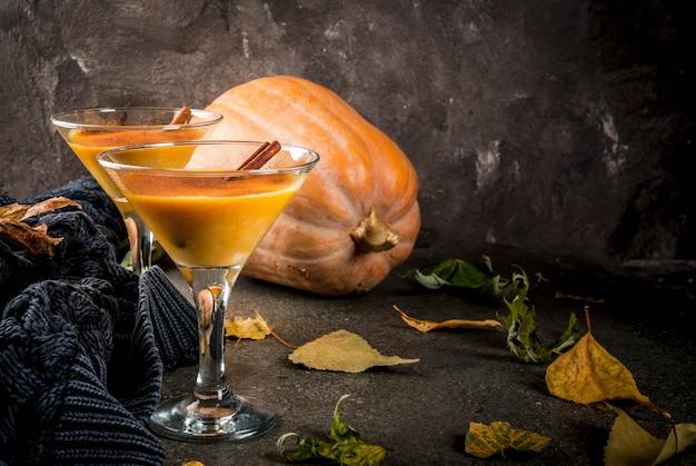 Boissons d'automne et d'hiver. cocktails de thanksgiving et halloween. margarita tarte à la citrouille avec bâton de cannelle, sur une table en pierre noire. maison confortable, avec des feuilles d'automne, plaid, citrouille, espace copie
