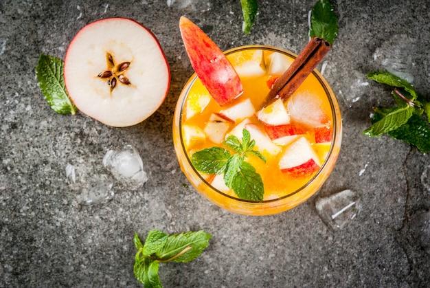 Boissons d'automne traditionnelles, cocktails mojito au cidre de pomme à la menthe, à la cannelle et à la glace. sur la table en pierre noire, copie vue de dessus de l'espace