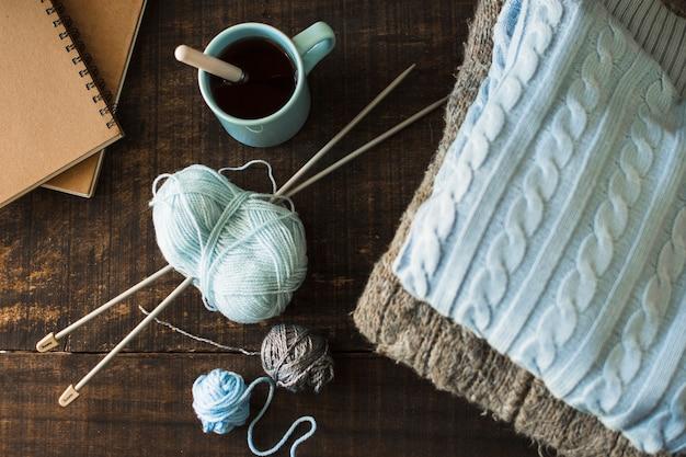 Boissons et cahiers près des fournitures de tricot et des vêtements chauds