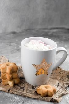 Boissons chaudes d'hiver avec des biscuits en forme d'étoiles sur un fond de béton minable