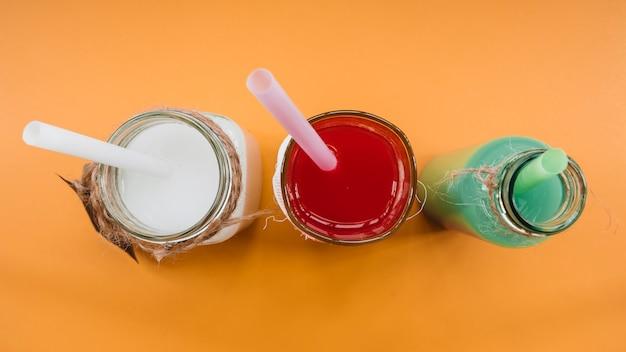 Boissons de différentes couleurs dans des bouteilles avec des pailles sur fond orange