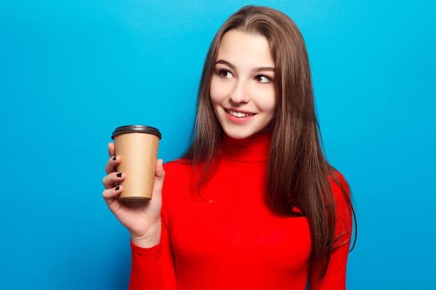 Boissons, émotions, gens, beauté, concept de mode de vie - belle femme émotionnelle heureuse en blouse rouge sur fond bleu studio buvant du café dans une tasse en papier souriant, positif, appréciant, nourriture du matin