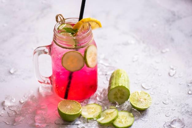 Boissons d'été exotiques rafraîchissantes de verres de boissons froides pot de fruits et légumes frais sur glace thé cocktail maison avec mojito citron vert et concombre, boisson d'été colorée rose rouge juteuse