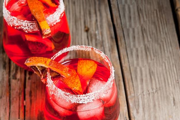 Boissons d'été rafraîchissantes. cocktail margarita orange sanglante, dans des verres sur une table rustique en bois avec une garniture d'orange.