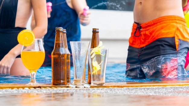 Boissons et jus de fruits avec cocktails exotiques et bouteille de bière installée sur la piscine.