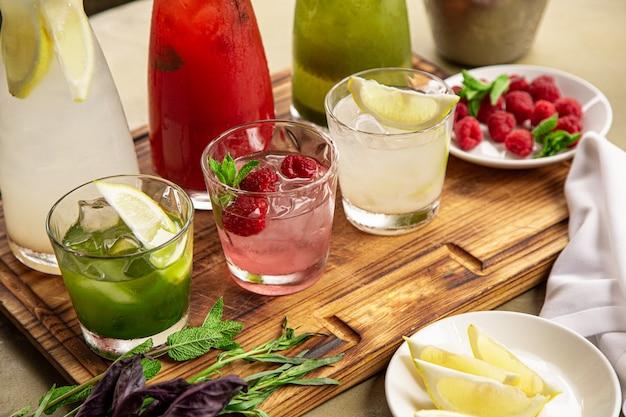 Boissons non alcoolisées estivales, un ensemble de limonades. des limonades dans des pichets sur la table, autour desquelles sont disposés les ingrédients.
