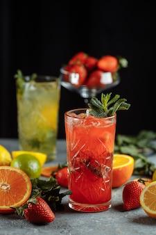 Boissons rafraîchissantes colorées pour l'été, jus de limonade aux fraises froid avec des glaçons dans les verres garnis de citrons frais tranchés.